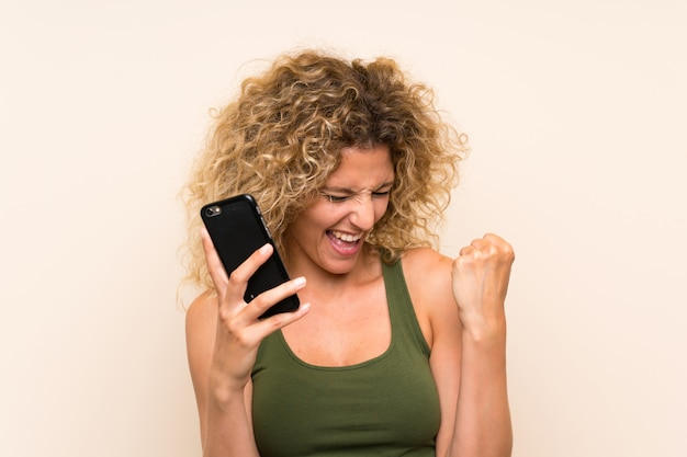 Jonge blondevrouw met krullend haar die mobiele telefoon met behulp van die een overwinning vieren