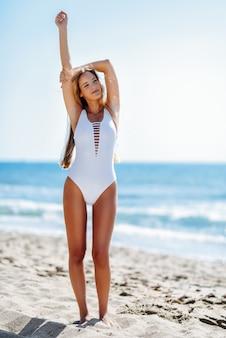 Jonge blondevrouw met mooi lichaam in wit zwempak op een tropisch strand.