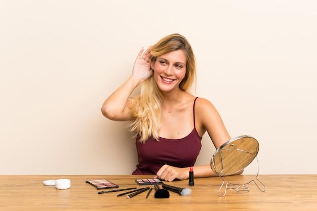 Jonge blondevrouw met schoonheidsmiddel in een lijst die iets luistert