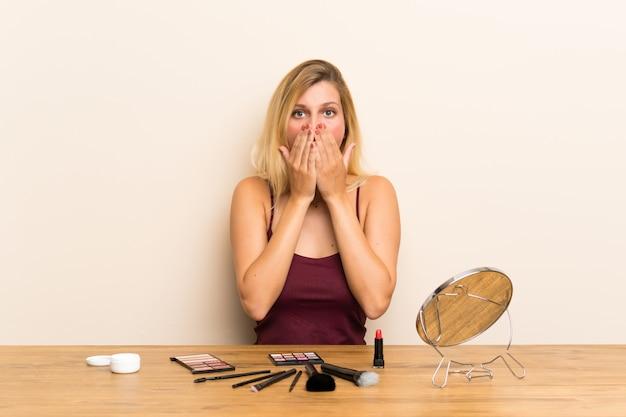 Jonge blondevrouw met schoonheidsmiddel in een lijst met verrassingsgelaatsuitdrukking