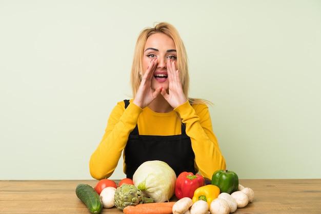 Jonge blondevrouw met veel groenten die met wijd open mond schreeuwen