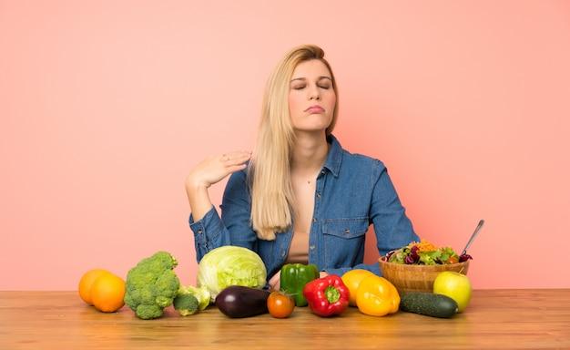 Jonge blondevrouw met vele groenten met vermoeide en zieke uitdrukking