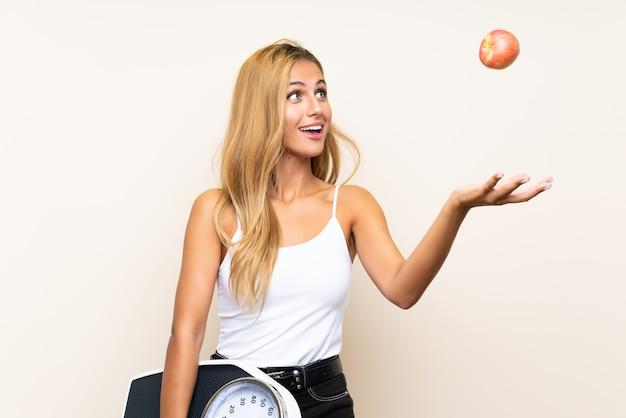 Jonge blondevrouw met weegmachine en met een appel