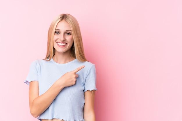 Jonge blondevrouw op roze en muur die opzij glimlachen richten, die iets tonen op lege ruimte.