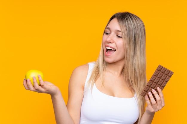 Jonge blondevrouw over blauw die een chocoladetablet in één hand nemen en een appel in de andere