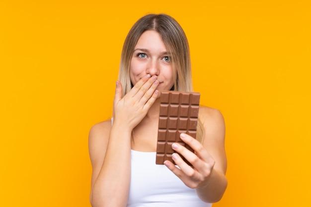 Jonge blondevrouw over blauw die een chocoladetablet nemen en verrast