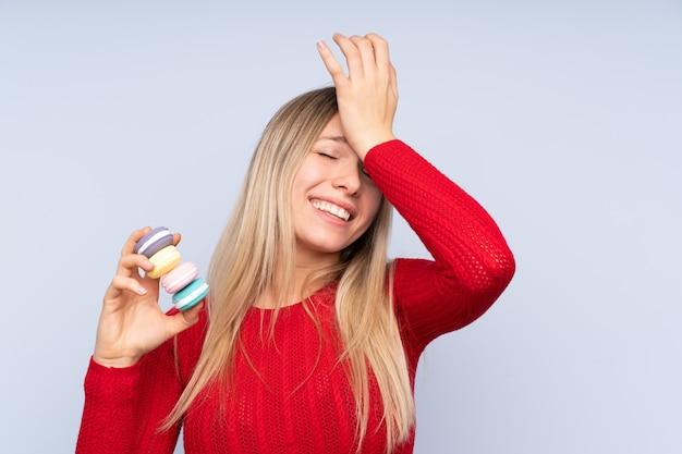 Jonge blondevrouw over blauw die kleurrijke franse macarons houden en de oplossing voornemen