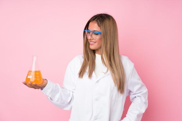 Jonge blondevrouw over geïsoleerd met een wetenschappelijke reageerbuis