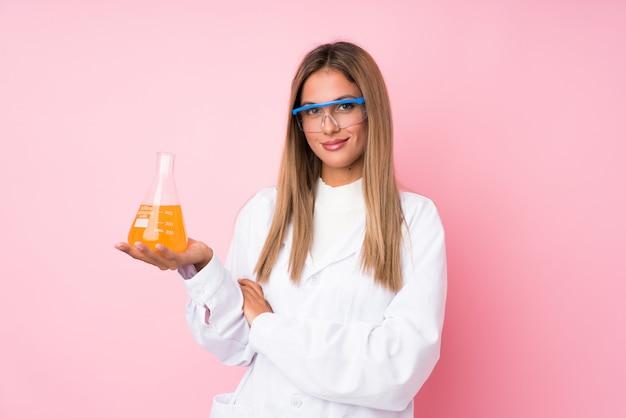 Jonge blondevrouw over geïsoleerd roze met een wetenschappelijke reageerbuis