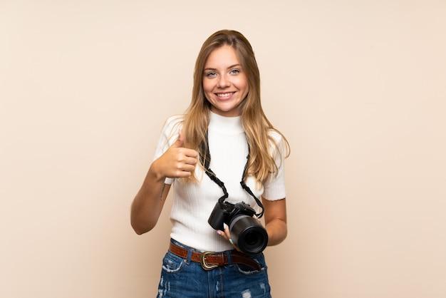 Jonge blondevrouw over geïsoleerde achtergrond met een professionele camera en met omhoog duim