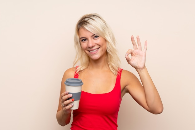 Jonge blondevrouw over geïsoleerde achtergrondholdingskoffie weg te nemen terwijl het maken van ok teken