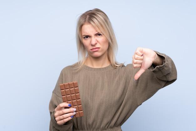 Jonge blondevrouw over geïsoleerde blauwe muur die een chocoladetablet nemen die slecht signaal maken