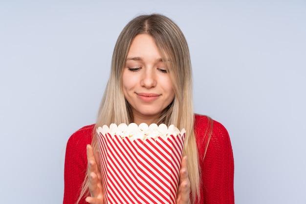 Jonge blondevrouw over geïsoleerde blauwe muur die een grote emmer popcorns houden