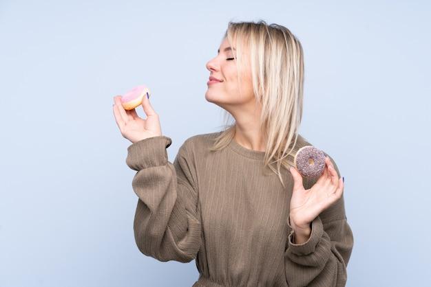 Jonge blondevrouw over geïsoleerde blauwe wallholding donuts met gelukkige uitdrukking