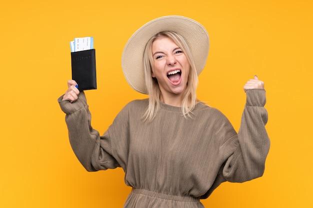 Jonge blondevrouw over geïsoleerde gele muur gelukkig in vakantie met paspoort en vliegtuigtickets