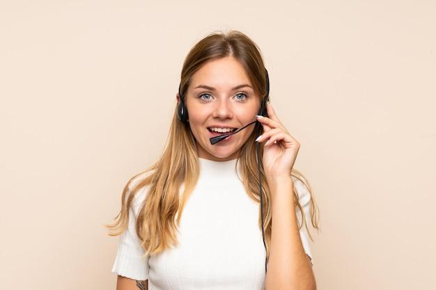 Jonge blondevrouw over geïsoleerde muur die met hoofdtelefoon werkt