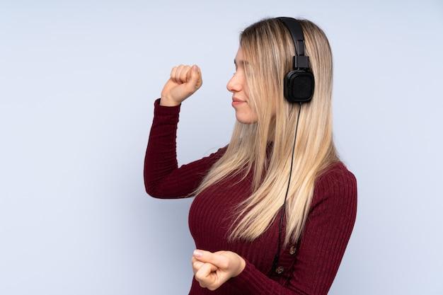 Jonge blondevrouw over geïsoleerde muur het luisteren muziek en het dansen