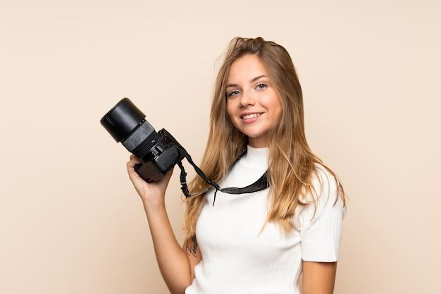 Jonge blondevrouw over geïsoleerde muur met een professionele camera