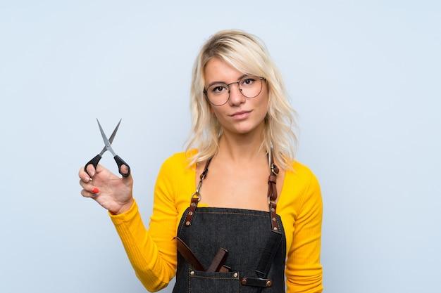 Jonge blondevrouw over geïsoleerde muur met kapper of kapperskleding