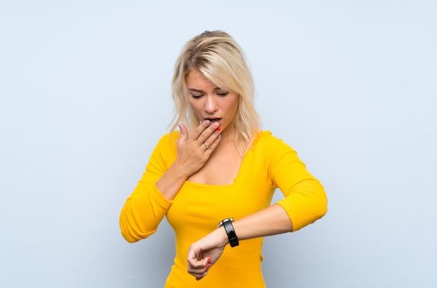 Jonge blondevrouw over geïsoleerde muur met polshorloge en verrast