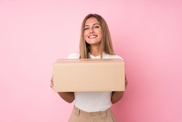 Jonge blondevrouw over geïsoleerde roze muur die een doos houden om het naar een andere plaats te verplaatsen