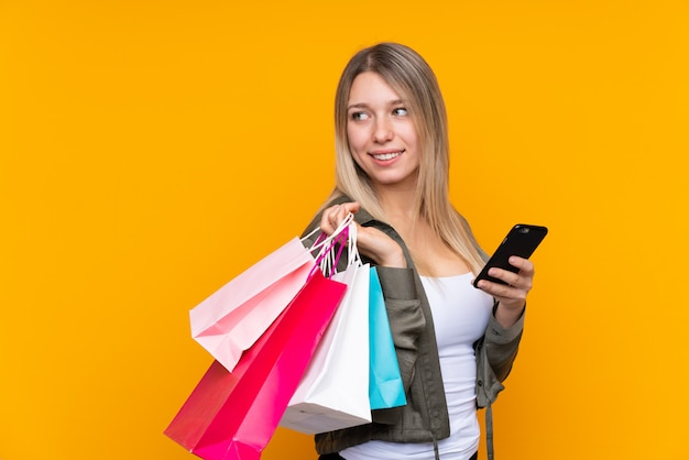 Jonge blondevrouw over gele holding het winkelen zakken en een mobiele telefoon