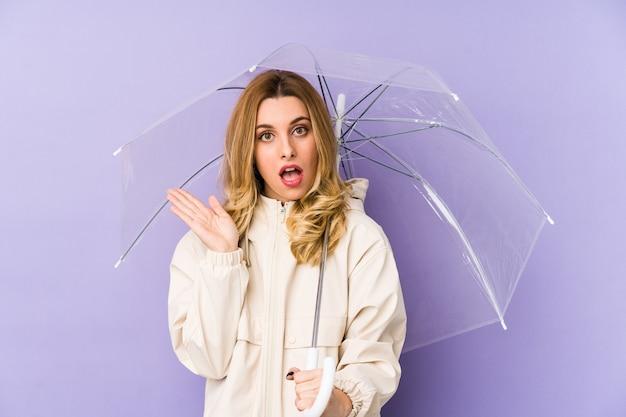 Jonge bloverde vrouw met een paraplu geïsoleerd jonge bloverde vrouw met een paraplu geïsoleerd verrast en geschokt.