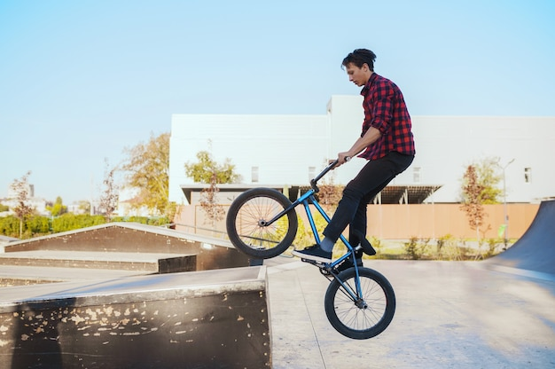 Jonge bmx-fietser doet truc, traint in skatepark. extreme fietssport, gevaarlijke fietsoefening, risico op straatrijden, fietsen in een zomerpark