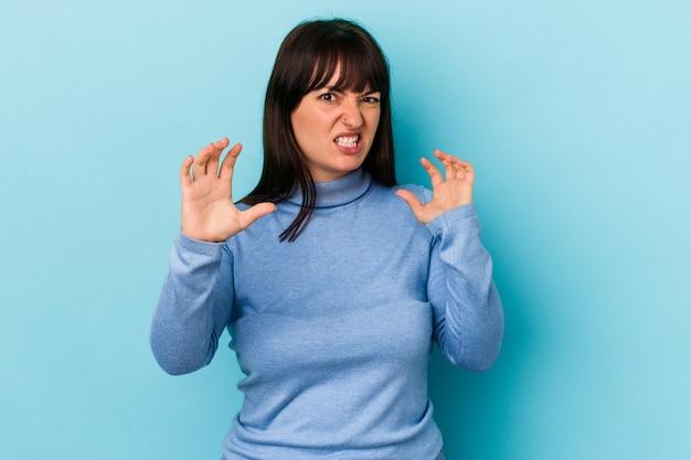 Jonge bochtige blanke vrouw geïsoleerd op blauwe achtergrond boos schreeuwen met gespannen handen.