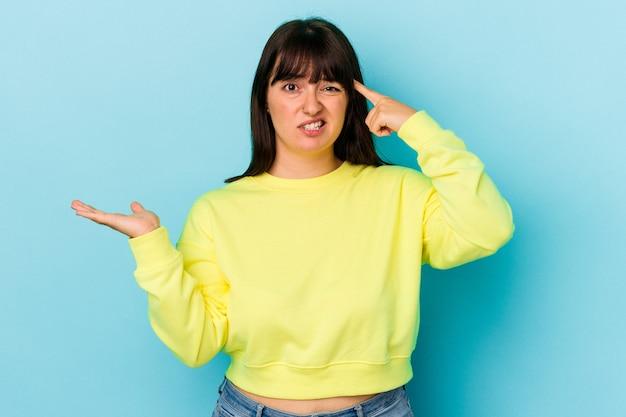 Jonge bochtige blanke vrouw geïsoleerd op blauwe achtergrond houden en tonen van een product bij de hand.