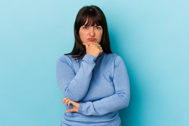 Jonge bochtige blanke vrouw geïsoleerd op blauwe achtergrond verdacht, onzeker, u te onderzoeken.