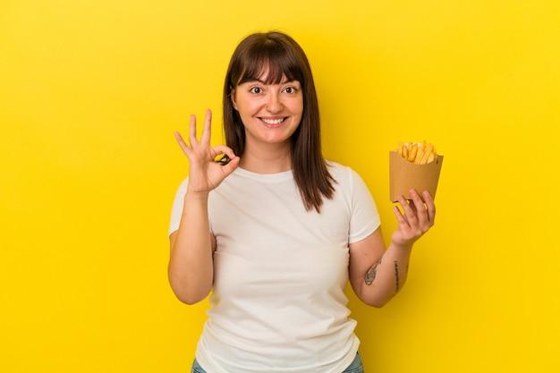 Jonge bochtige blanke vrouw met frietjes geïsoleerd op gele achtergrond vrolijk en zelfverzekerd met een goed gebaar.