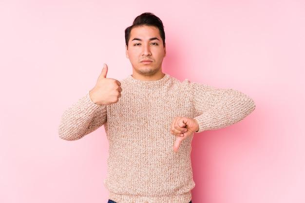 Jonge bochtige man poseren in een roze geïsoleerd duimen opdagen en duimen omlaag, moeilijk kiezen concept