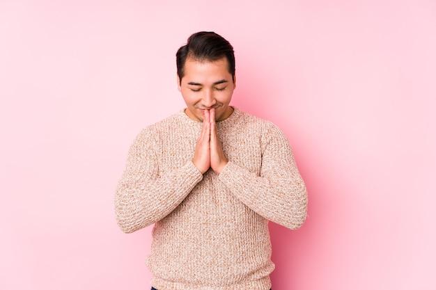 Jonge bochtige man poseren in een roze muur geïsoleerde hand in hand bidden in de buurt van de mond, voelt zich zelfverzekerd.