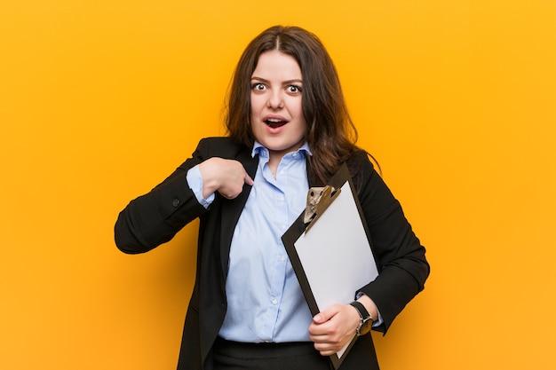 Jonge bochtige plus grootte bedrijfsvrouw die een klembord houdt verrast wijzend op zichzelf, breed glimlachend.