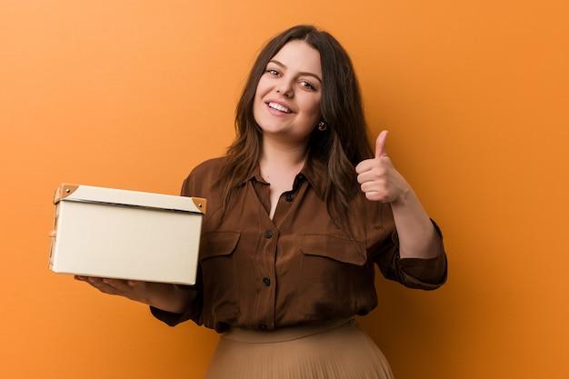 Jonge bochtige plus groottevrouw die een doos houdt glimlachend en duim opheft