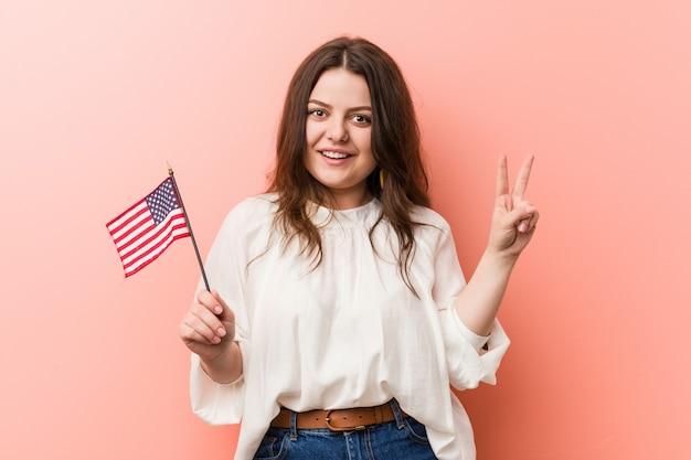 Jonge bochtige plus groottevrouw die een vlag houden die van verenigde staten nummer twee met vingers tonen.