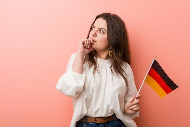 Jonge bochtige plus groottevrouw die een vlag van duitsland houdt die zijdelings met twijfelachtige en sceptische uitdrukking kijkt.