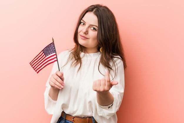 Jonge bochtige plus-groottevrouw die een vlag van verenigde staten houden die met vinger op u richten alsof uitnodigend dichterbij komen.