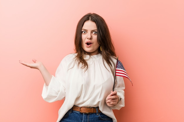 Jonge bochtige plus-groottevrouw die een vlag van verenigde staten onder de indruk houden