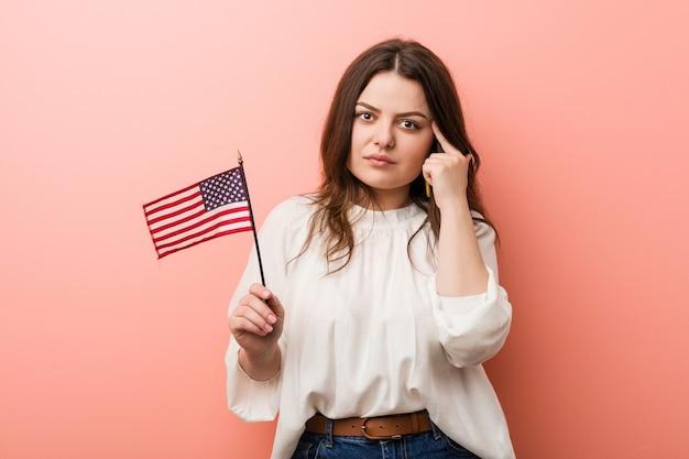 Jonge bochtige plus size vrouw die een vlag van de verenigde staten houdt die zijn tempel met de vinger richt, nadenkend, gericht op een taak.