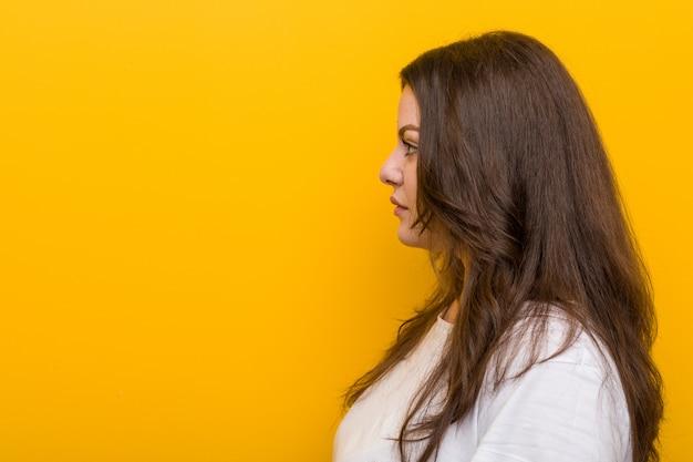 Jonge bochtige plus size vrouw kijkt naar links, zijwaarts poseren.