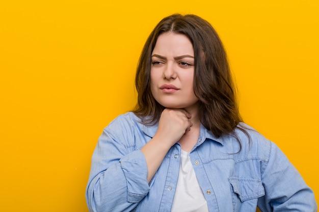 Jonge bochtige plus size vrouw lijdt pijn in de keel als gevolg van een virus of infectie.