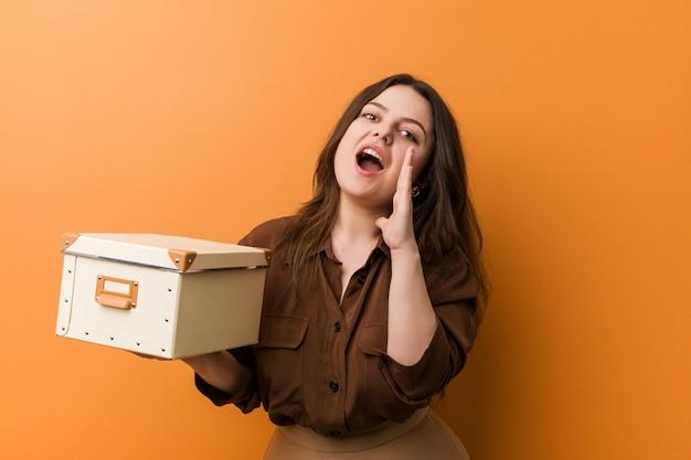 Jonge bochtige plus size vrouw met een doos schreeuwen opgewonden naar voren.