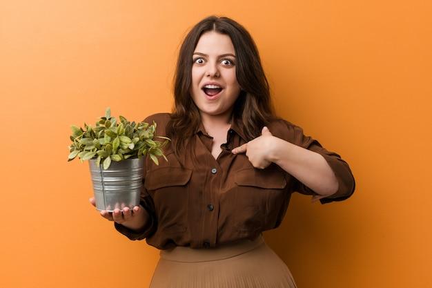 Jonge bochtige plus size vrouw met een plant verrast wijzend op zichzelf, breed glimlachend.