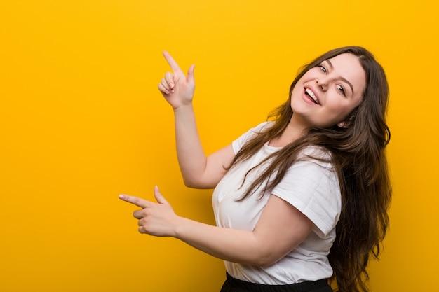 Jonge bochtige plus size vrouw opgewonden wijzend met wijsvingers weg.