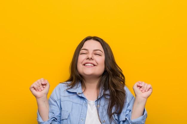 Jonge bochtige plus size vrouw verhogen vuist, gelukkig en succesvol voelen.