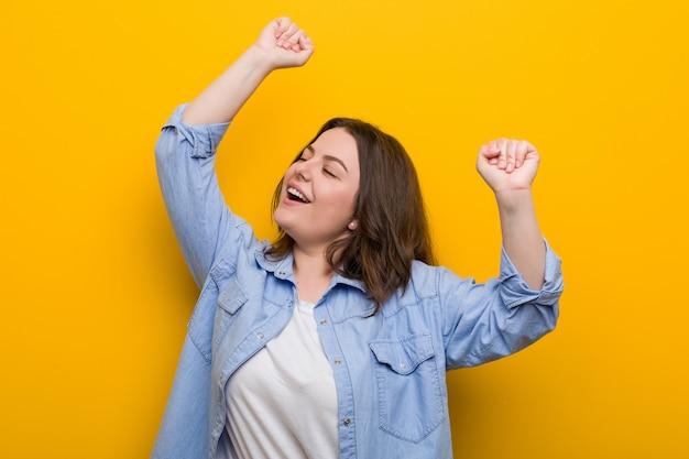 Jonge bochtige plus size vrouw viert een speciale dag, springt en heft armen met energie.