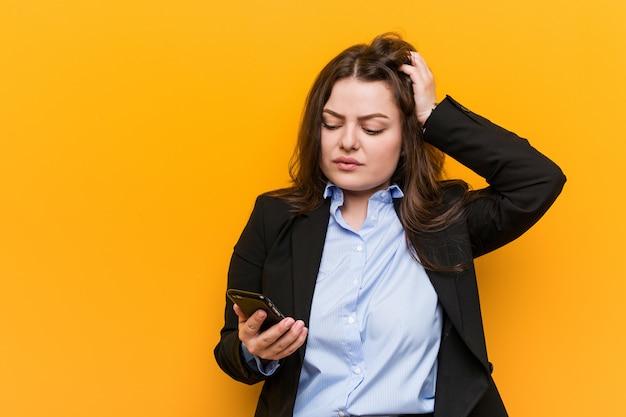 Jonge bochtige plus size zakenvrouw met een telefoon die geschokt is, ze heeft een belangrijke vergadering onthouden.