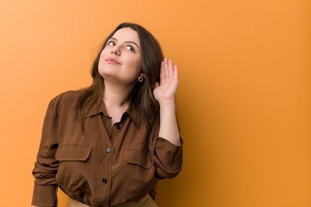 Jonge bochtige russische vrouw die aan het luisteren van een roddel probeert.